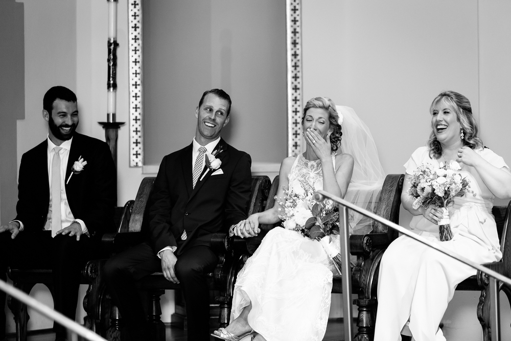 The bride and groom laugh during their Skaneateles church ceremony.
