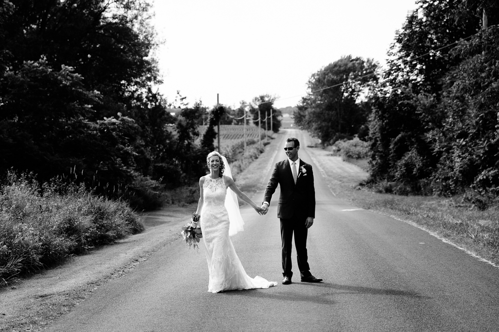 The bride and groom walk down a country road.