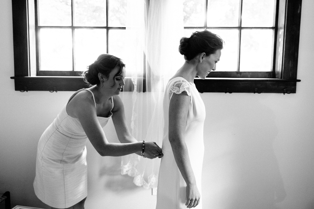 bride gets zippered into dress by maid of honor.