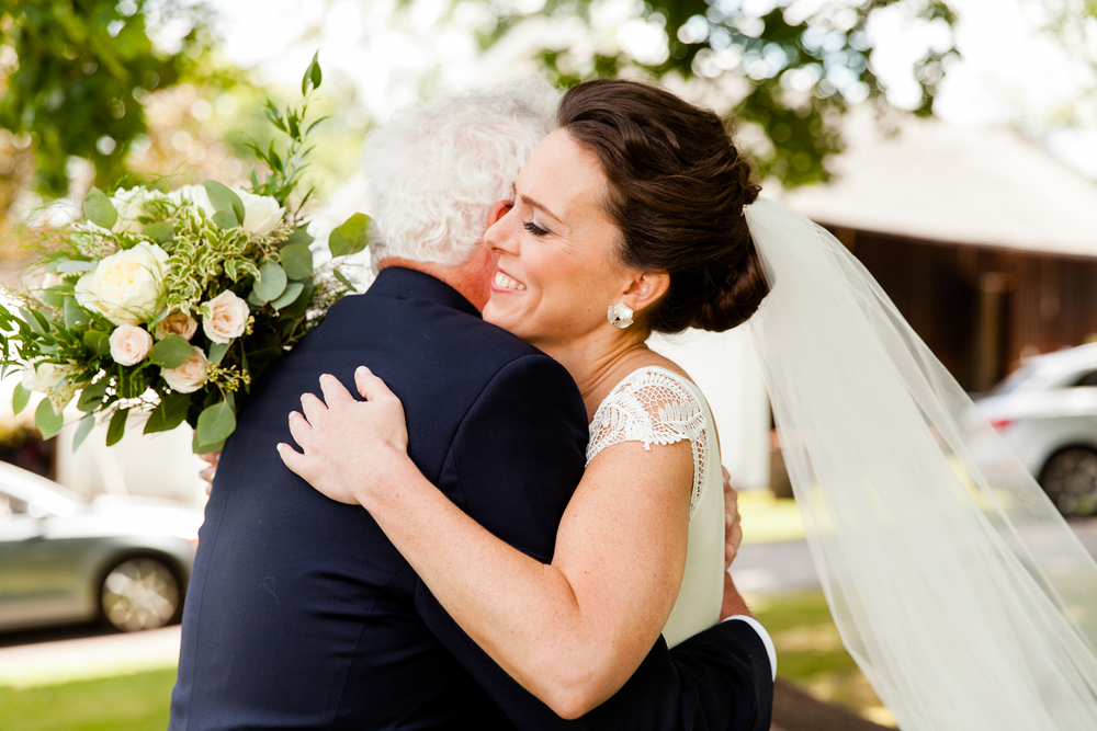 A bride hugs her father on her wedding day.