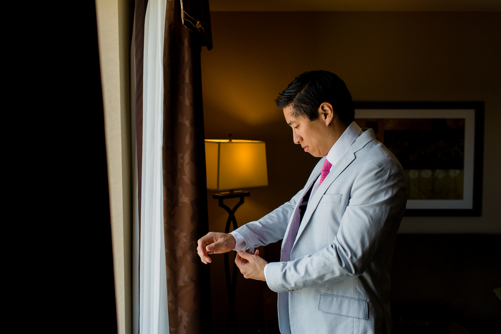 Groom adjusts his cufflink.