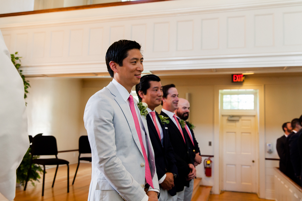 Groom watches bride walk down the aisle.