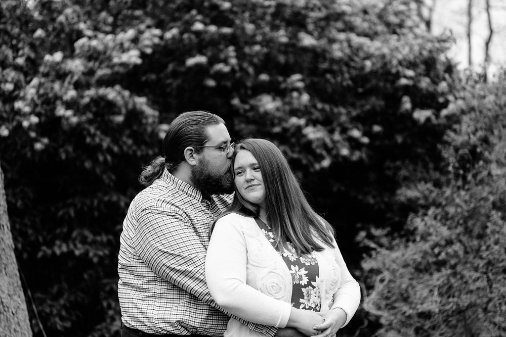 Black and White engagement photo man kissing side of womans head.