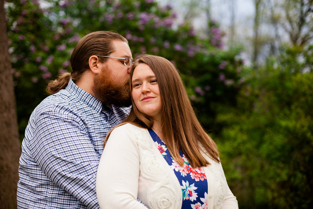 Woman smiles in Syracuse NY as man kisses side of her head. A romantic photograph with lilacs in the background.