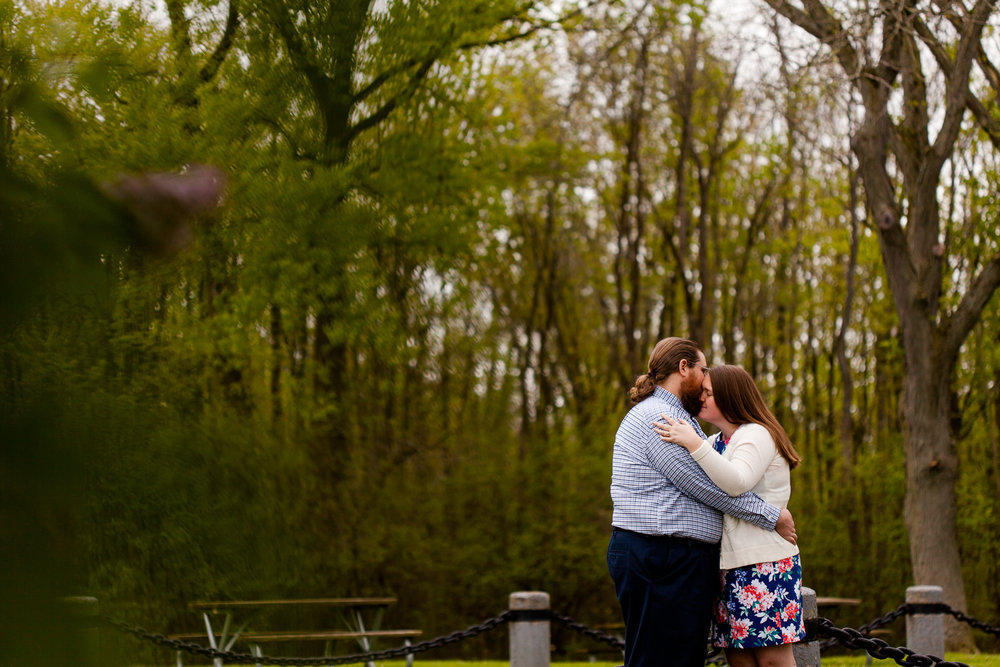 A sweet engagement photo of a woman in a blue floral dress and a man in a blue plaid shirt. They are at Onondaga Lake Park in Syracuse NY.