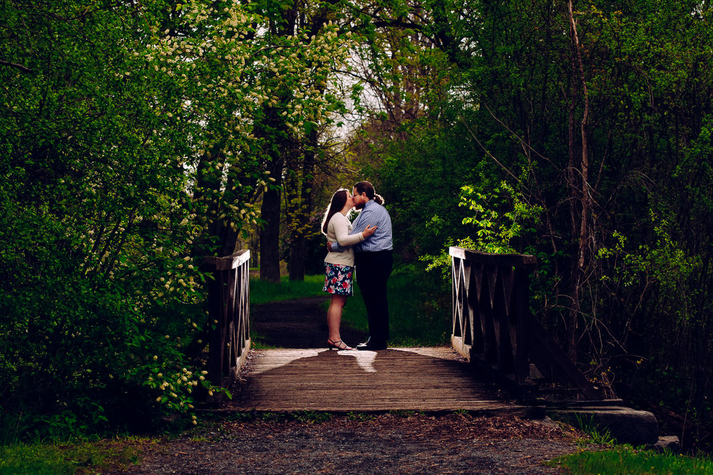 A man and woman kiss on a secluded bridge in the evening. They are lit from behind. It is very romantic and magical.