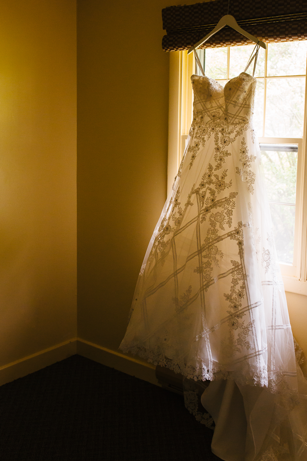 Full length wedding dress hangs in an empty room. The dress is white and lacey.