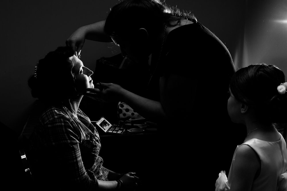Flower girl watches bride as she gets her make up done. A black and white image with dramatic lighting.