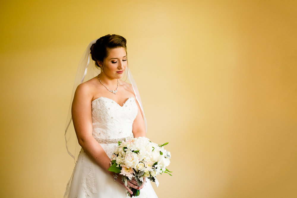 Bride looks down at her bouquet of white flowers. She is in a white wedding gown with a veil and she is standing against a stark yellow wall.