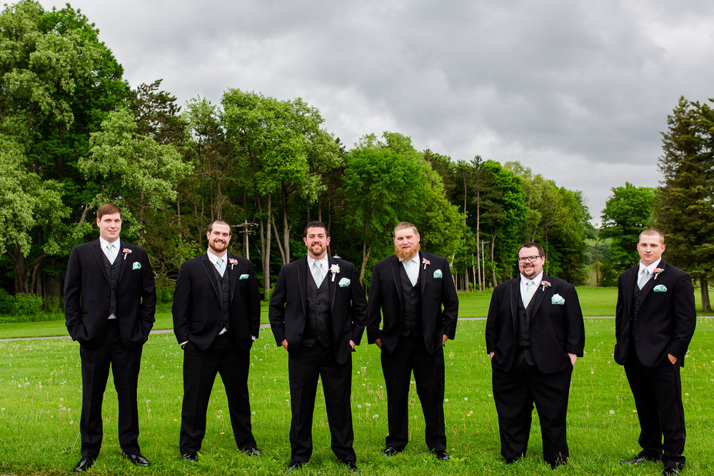 The groom and groomsmen stand in a line against a back drop of green trees. The sky is dark with clouds.