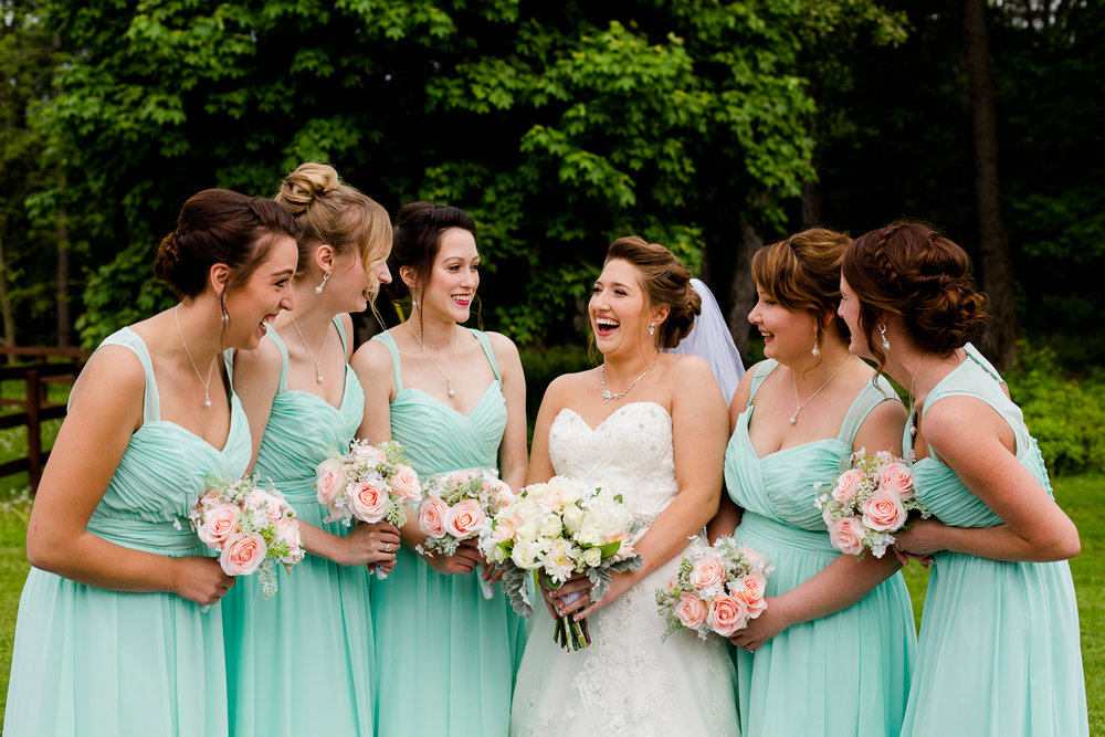 Bridesmaids stand together in light blue dresses laughing.