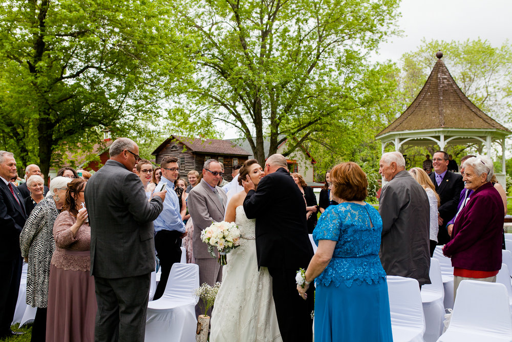 Father kisses bride on the cheek at the end of the aisle.
