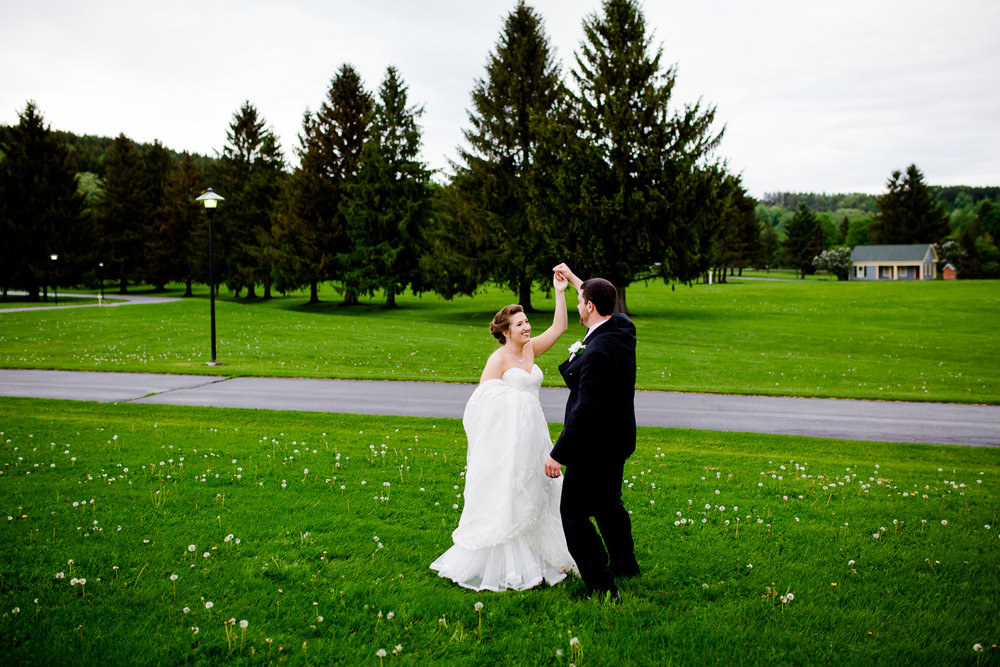Bride and groom twirl on green grass. There are white flowers around them. Pine trees are in the distance. The bride is holding her white lace wedding gown in one hand.