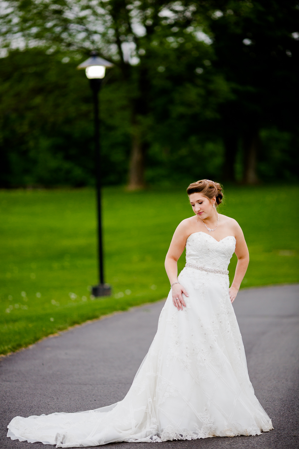 Portrait of a bride in a white wedding dress. She has a jewel belt around her waist. She is looking over her shoulder. There is green grass and a lamp post in the background.