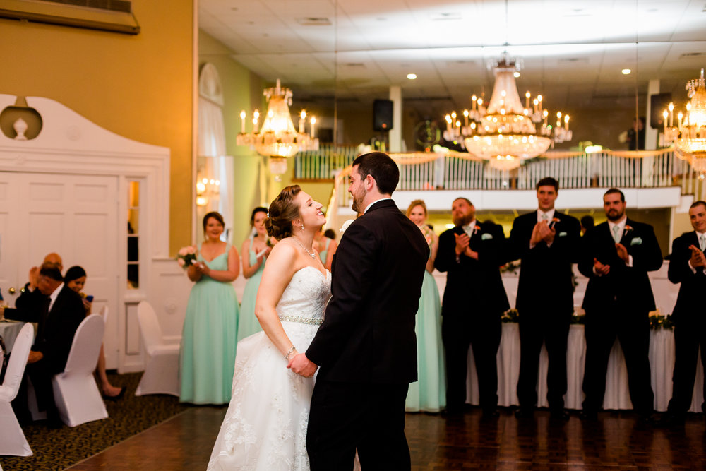 Bride and groom have first dance. Bride smiles at groom.