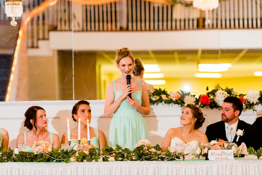 The maid of honor gives a speech. The bride looks up at her.