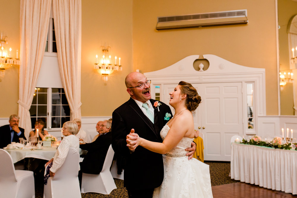 The bride and her father laugh during the father daughter dance at her wedding. They are in a large ball room.