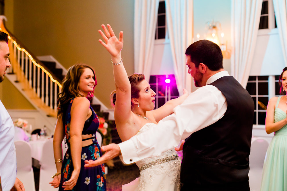 Bride and groom share a silly dance moment on at their wedding reception. The bride has her arms up in the air. Friends dance in the background.