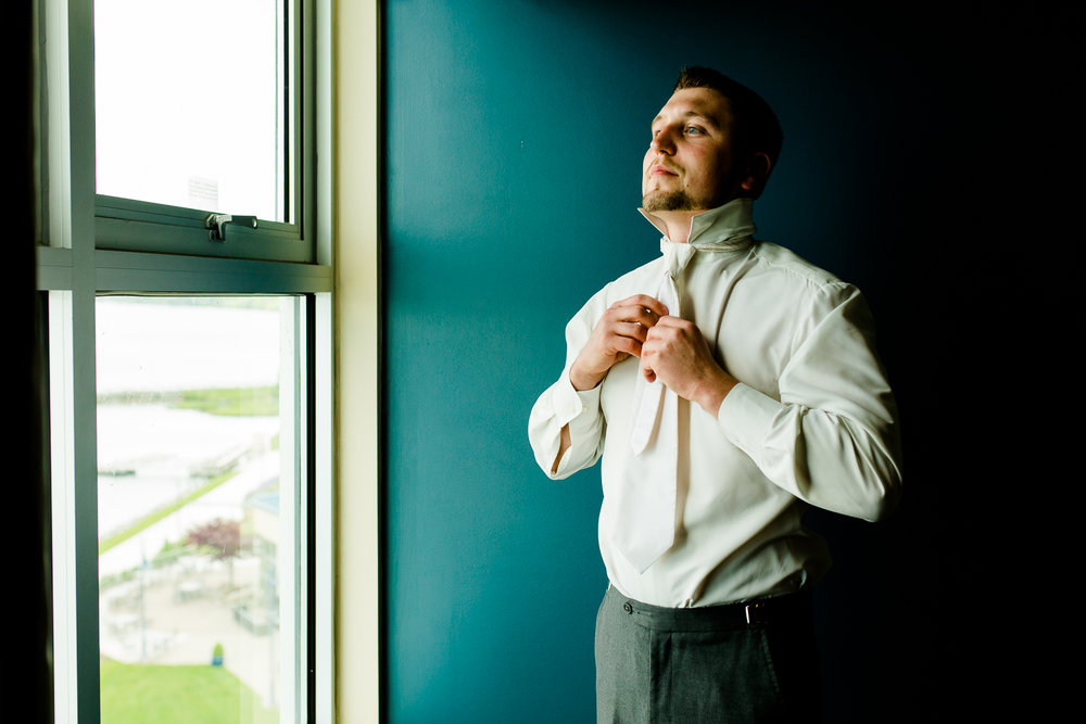 Groom adjusts tie against blue background. He is looking out of a window.