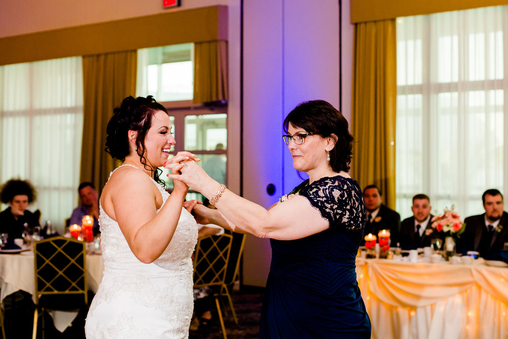 Bride laughs while dancing with her mother.