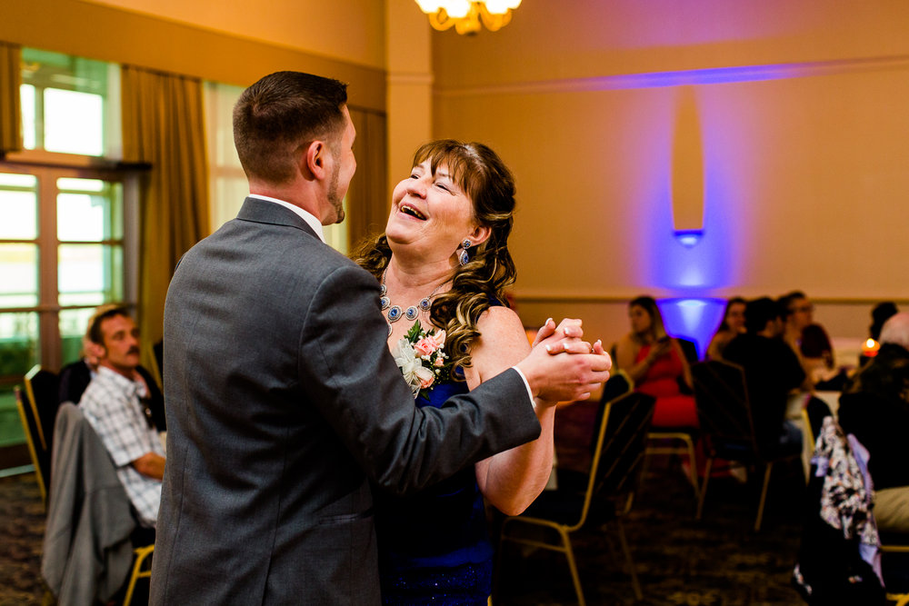 Mother son dance. The mother is laughing while dancing with the groom.