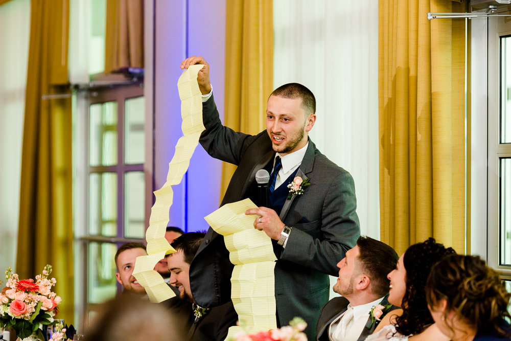 The best man holds up a giant speech as a joke.