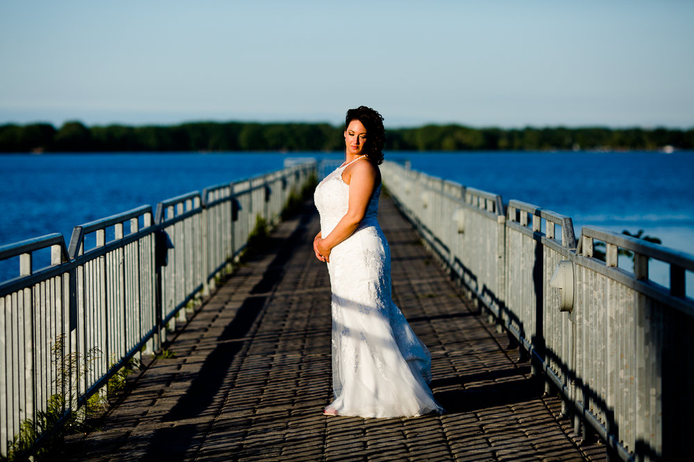 A bride in a white wedding dress stands in the center of a pier at sunset. The blue lake surrounds the pier. She looks over her shoulder.