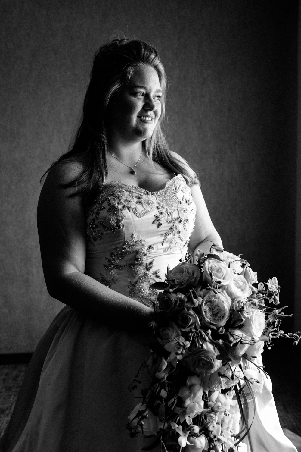 Black and white image of the bride holding her flowers. She looks out a window.