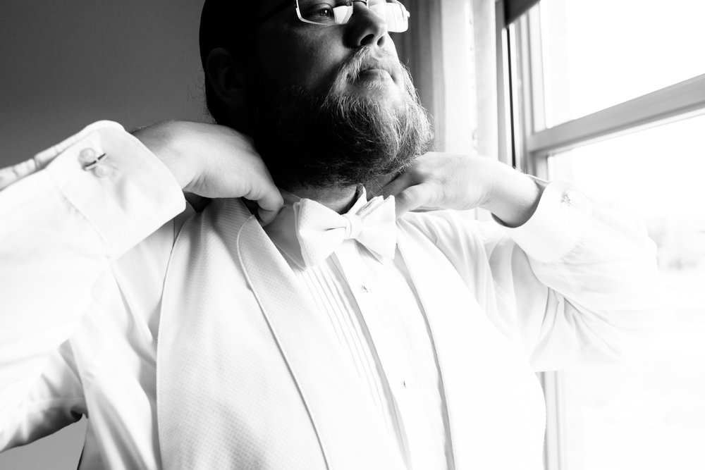Black and white image of a groom adjusting his bowtie.