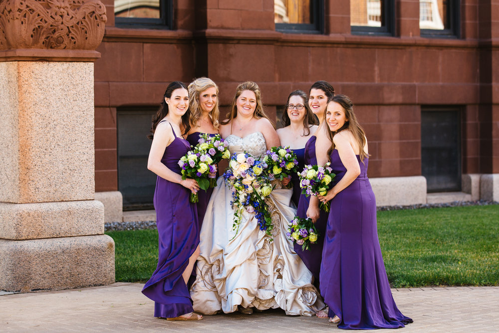 Bride in an Ivory wedding gown poses with bridesmaids in purple floor length dresses.