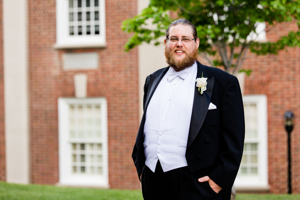Portrait of a groom. Black tux, white vest.