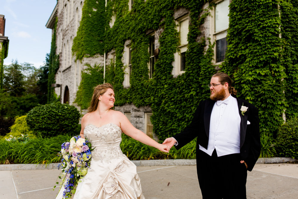 Portrait of the bride and groom. They are standing in front of a stone building with ivy growing on it. It is located at Syracuse University in Syracuse, NY.