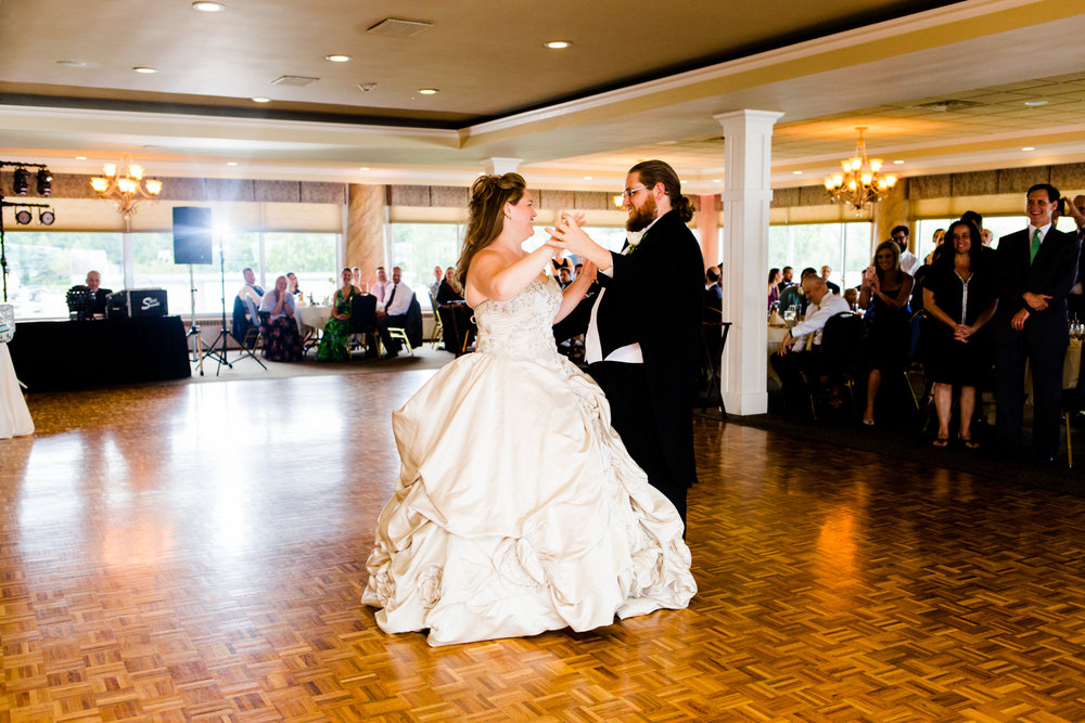 Bride and groom smile while sharing their first dance.