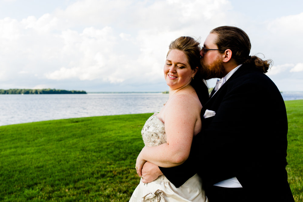 Groom kisses bride on the side of the head. They are standing in front of a lake.
