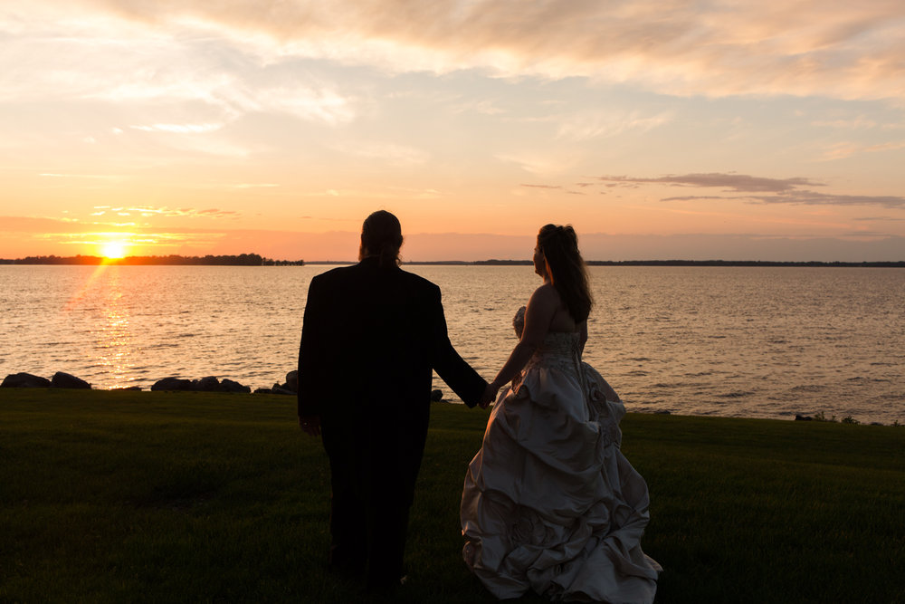 Bride and groom hold hands and watch the sunset across the lake.