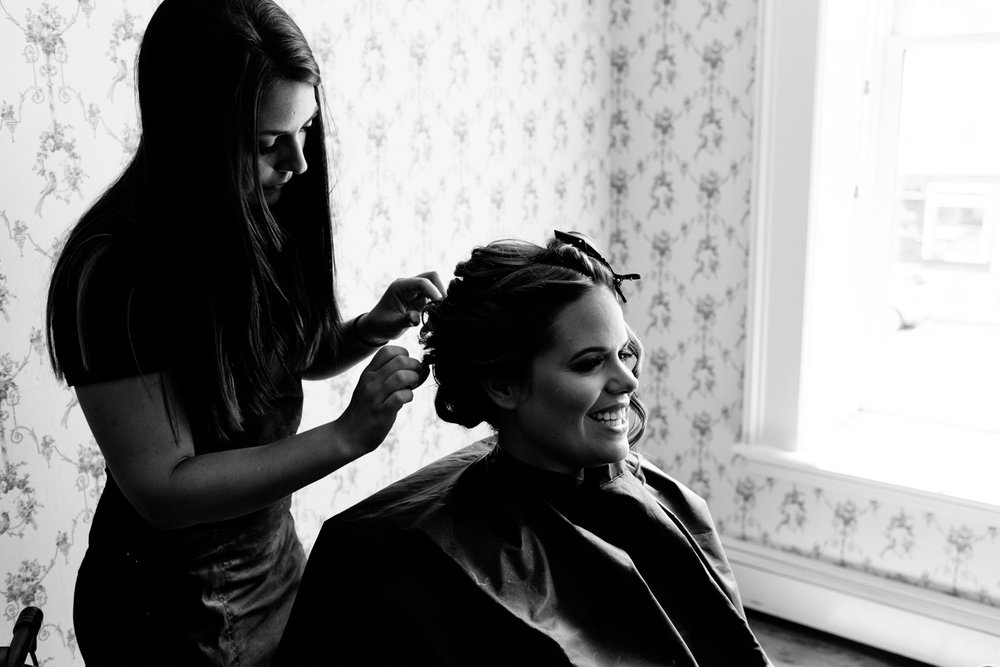 Black and white image of bride getting her hair done.