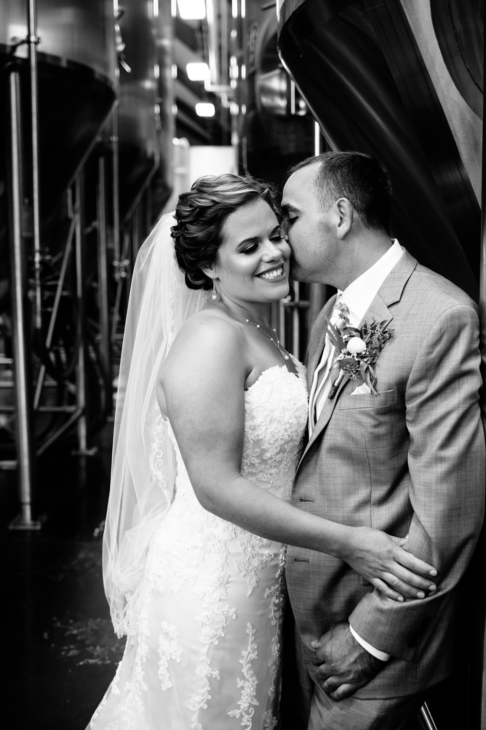 Black and white image of bride leaning into groom while he gives her a kiss on the cheek.