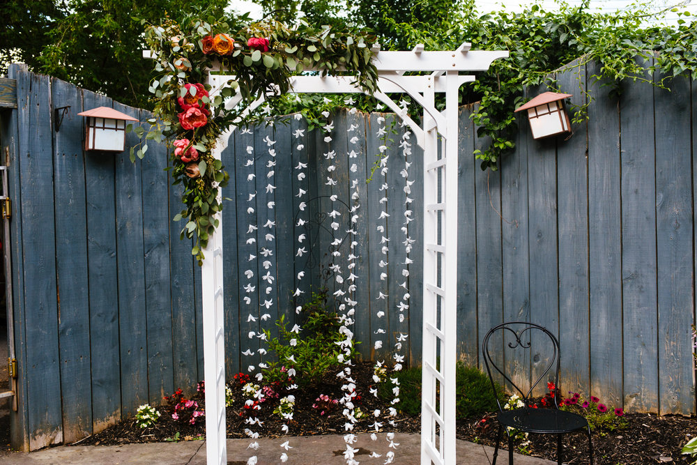 Wedding ceremony arbor adorned with flowers.