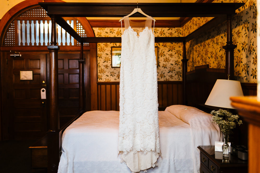 Lace wedding gown hanging from four poster bed.