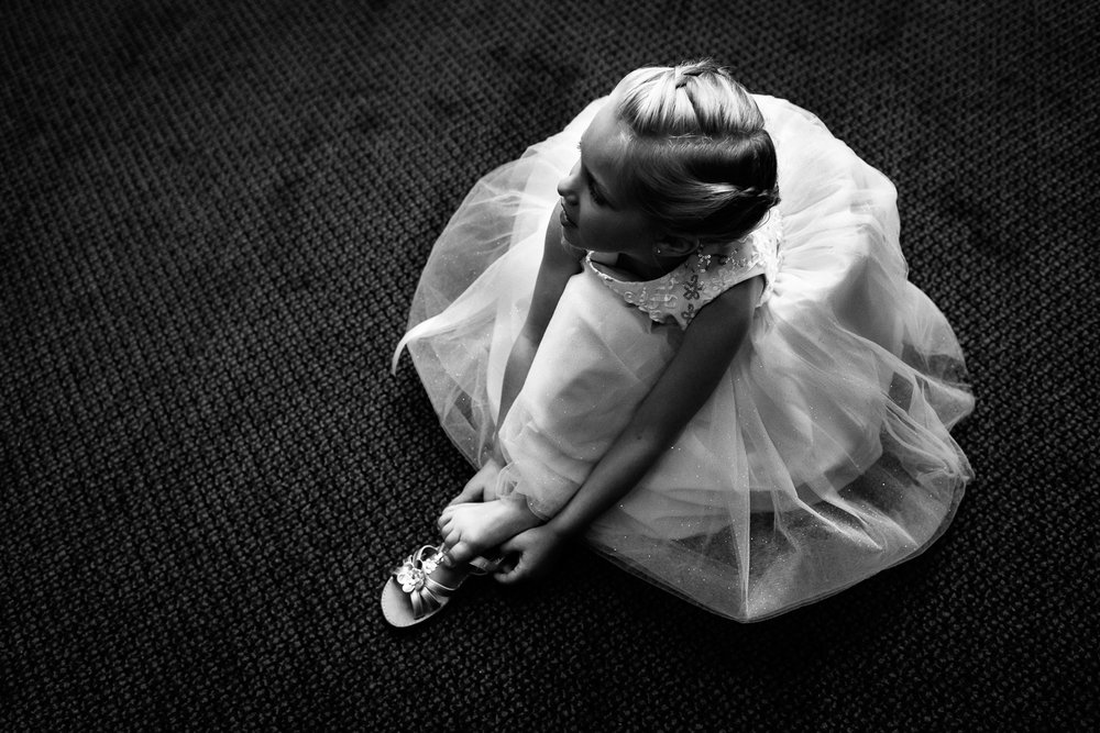 Black and white image of flower girl putting her shoe on.