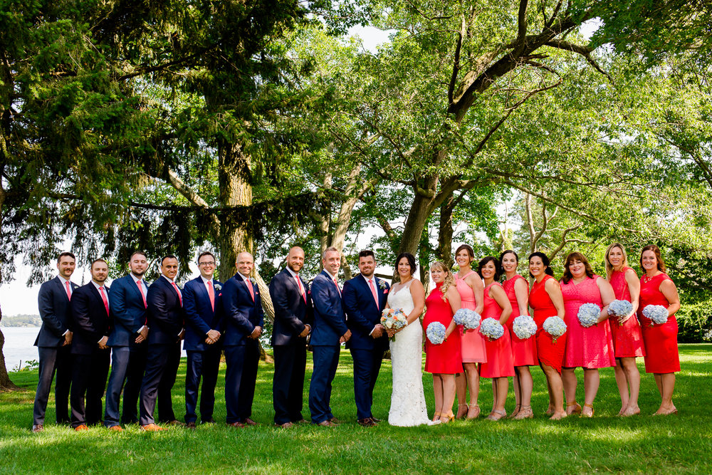 Bridal party stands in a line with trees and a lake behind them. They are on the lawn of Belhurst Castle.