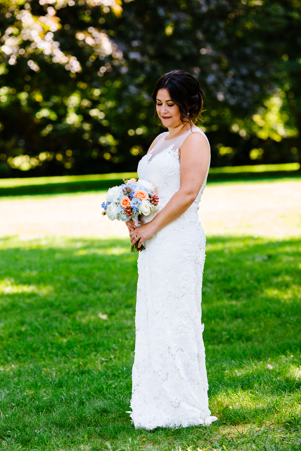 Full length portrait of the bride looking down at her flowers.