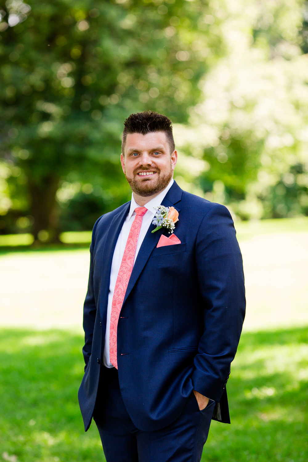 Portrait of the groom in a navy suit and coral tie.