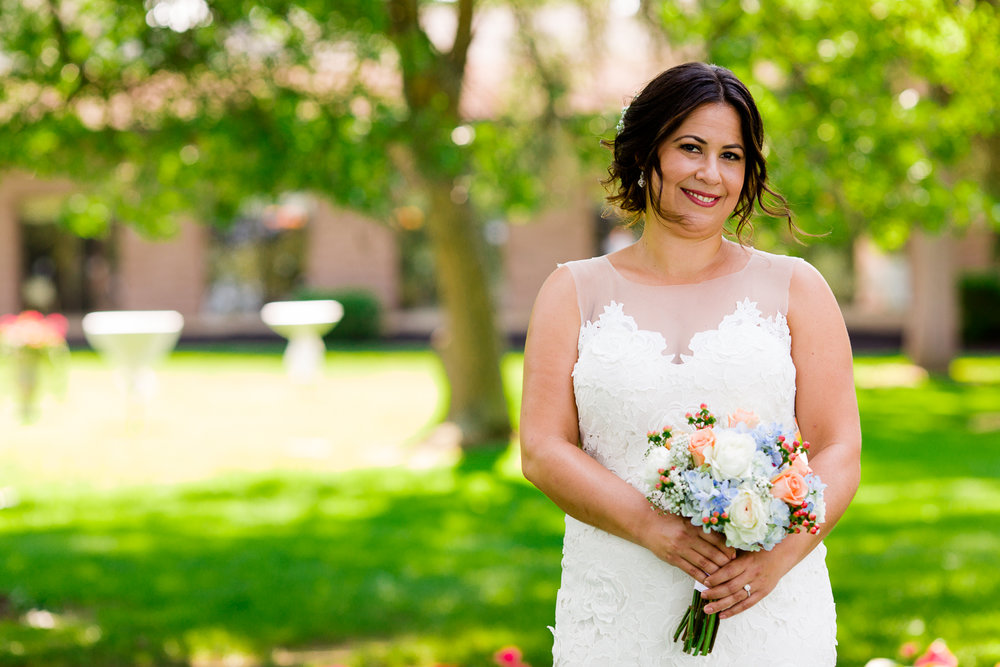 Portrait of a bride wearing a white lace wedding gown. She is holding a bouquet of flowers that are white, coral, and light blue.