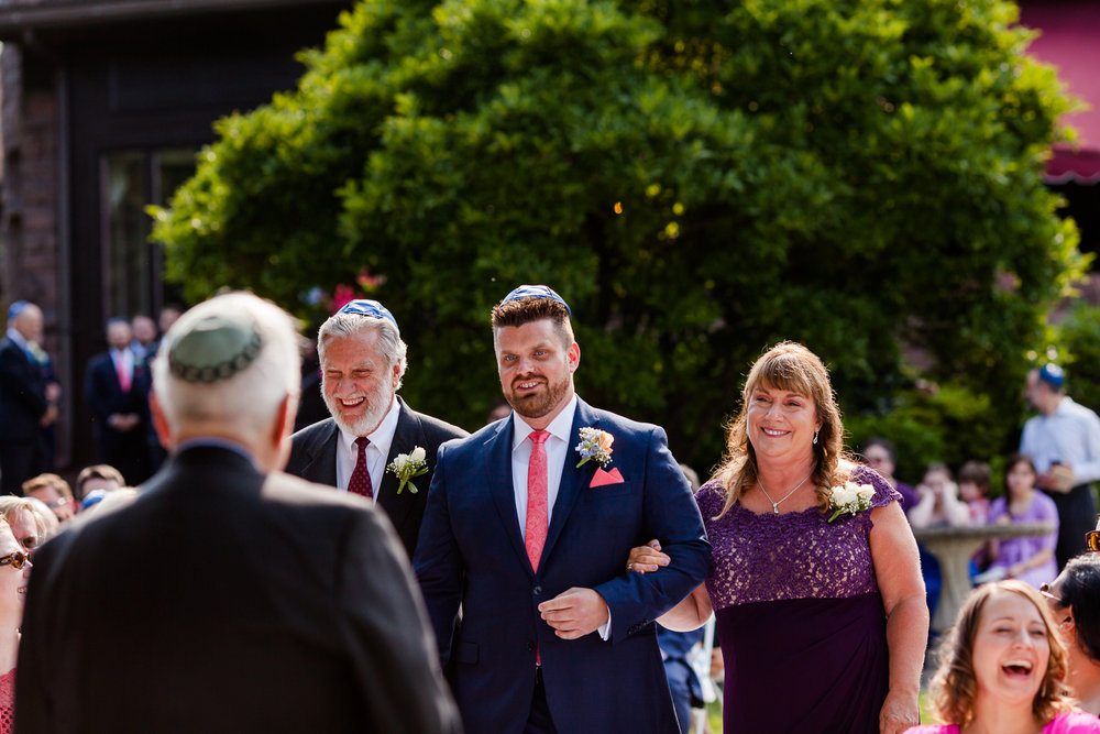 Groom walks down aisle with parents.
