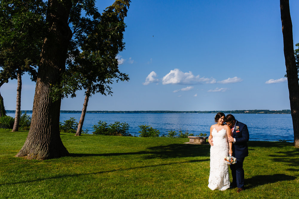Groom kisses bride on the shoulder. The sky and lake are blue behind them.