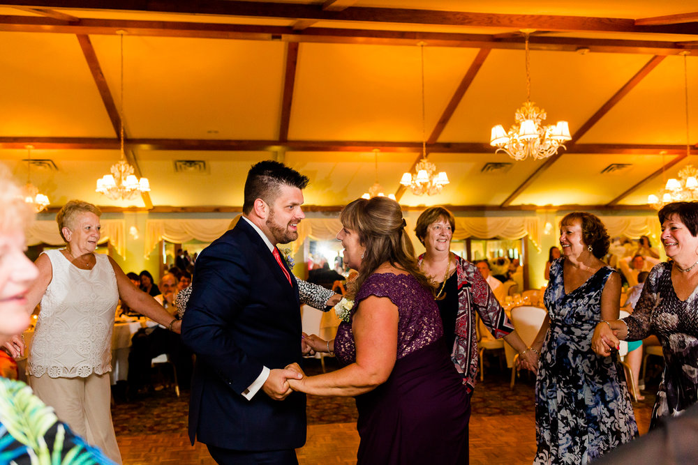 Groom and mother dance while a circle of friends surround them.