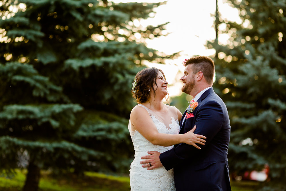 Bride and groom portrait at sunset. Pine trees are in the background.