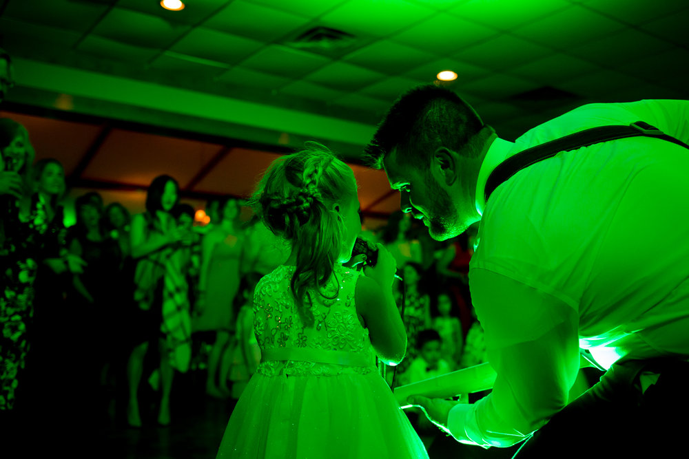 Groom plays guitar with flower girl during wedding reception.