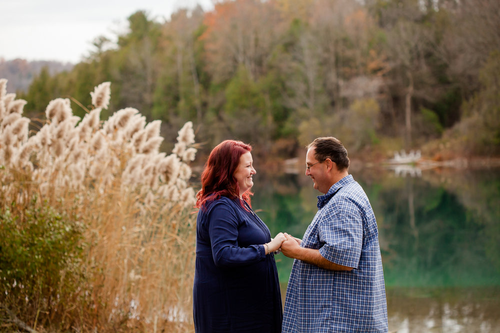 Man and woman hold hands during their engagement session at Green Lakes State Park.